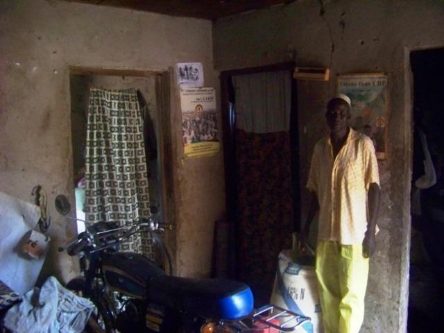 Saïdou Tagnan in his living room, next to his motorcycle.